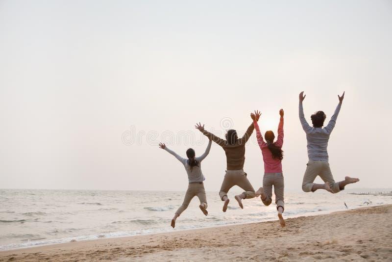 Junge Freunde, die am Strand springen stockbild