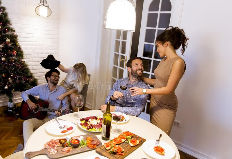 Junge Freunde, die zu Hause Weihnachts- oder Sylvesterabend feiern stockbilder