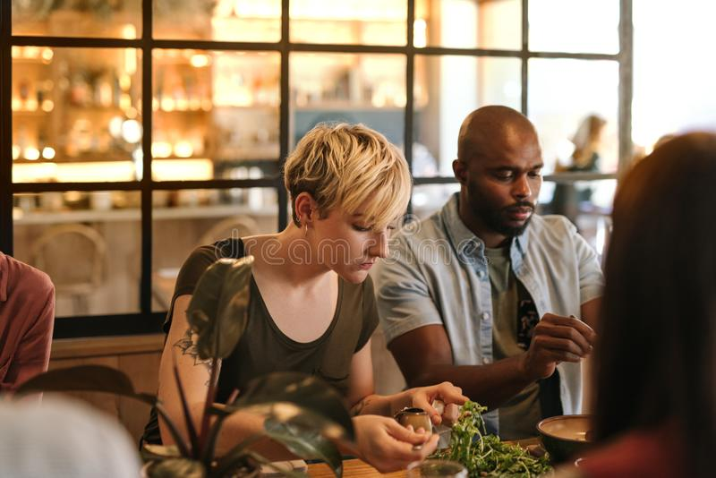 Junge Freunde, die zusammen in einer modischen Bistro essen lizenzfreie stockfotografie