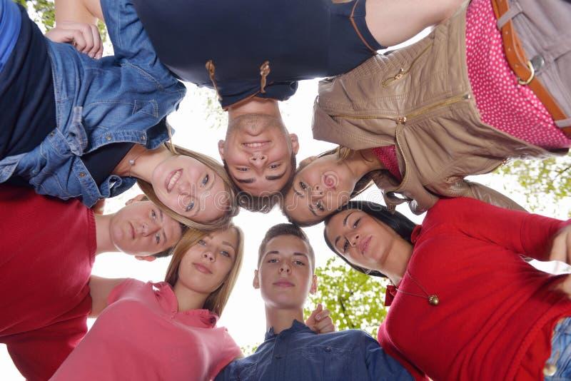 Junge Freunde, die zusammen im Park im Freien bleiben lizenzfreie stockfotos