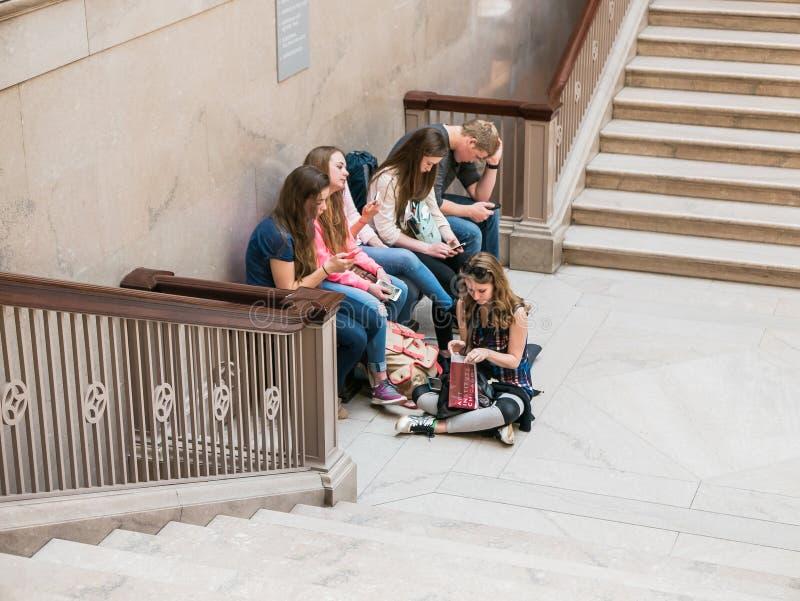 Junge Freunde entspannen sich auf Prunktreppe bei Art Institute von chica stockfotos