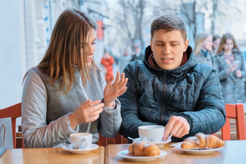 Junge Freunde Mann und Frau, die in des im Freien trinkendem Teekaffee Cafés mit Hörnchen sprechen lizenzfreie stockfotos