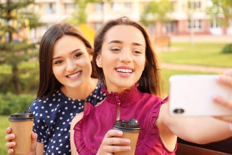 Junge Freunde mit den Tasse Kaffees, die draußen selfie nehmen lizenzfreie stockfotografie