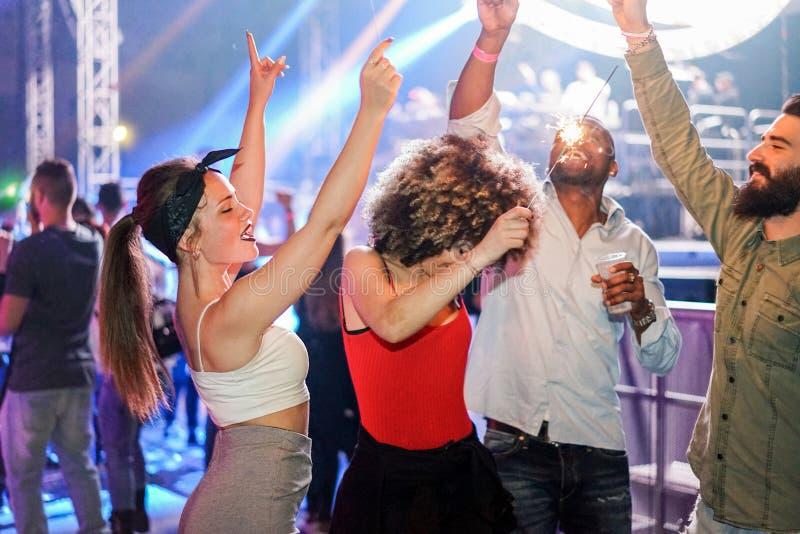Junge Freunde tanzen bei Nachtklub-Festival-Party mit Dj im Hintergrund - Happy people have fun inside disco - Nightlife stockfotografie
