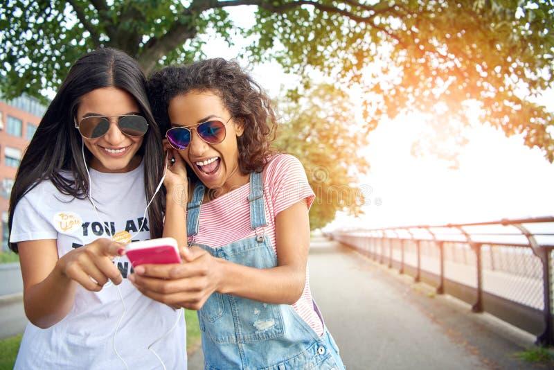 Junge Freundinnen, die außerhalb Musik zusammen hören an gehen stockbild