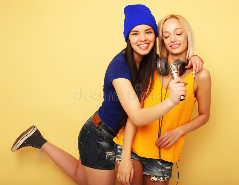Junge Freundinnen mit Mikrofon lizenzfreie stockfotografie