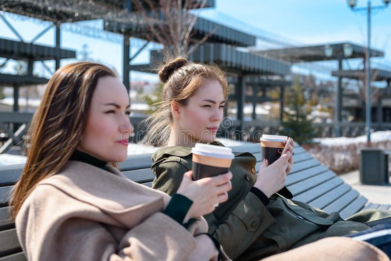 Junge Freundinnen sitzen auf einer Bank auf der Straße von Kasan und trinken Kaffee mit einer Bistro stockbilder