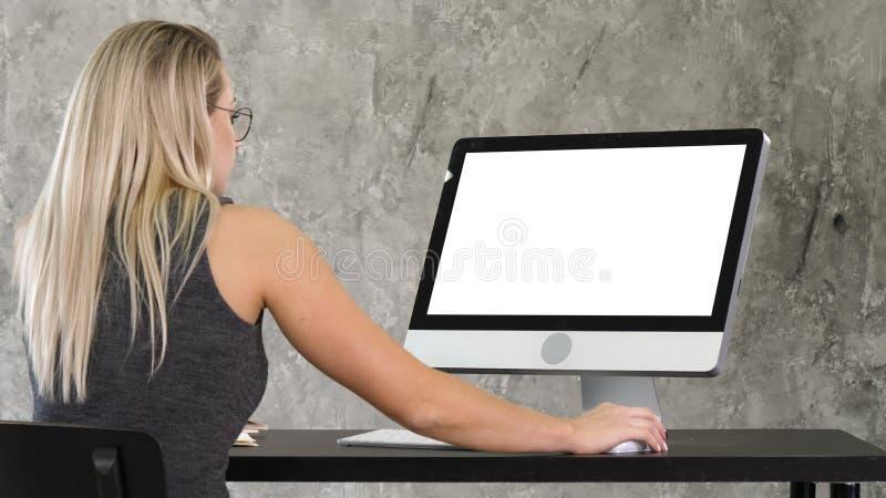 Junge freundliche Betreiberfrau, die an dem Computer spricht und arbeitet Weiße Bildschirmanzeige stockfoto