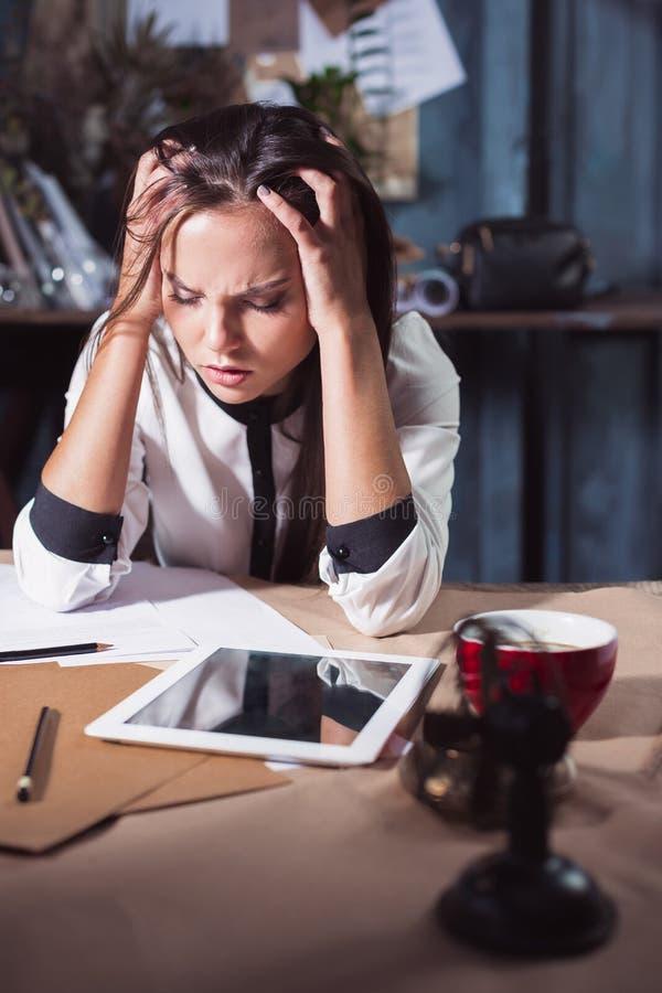 Junge frustrierte Frau, die am Schreibtisch vor Laptop arbeitet lizenzfreies stockfoto