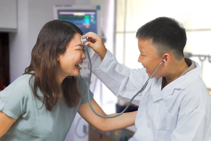 Junge fungiert wie eine Doktorkontrolle seine Mutter stockfotos