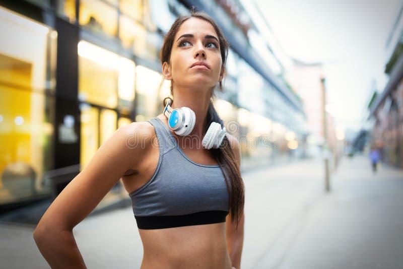 Junge geeignete Frau, die Musik hört und durch Betrieb ausarbeitet lizenzfreie stockbilder