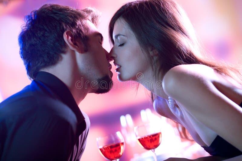 Junge Geliebte, die in der Gaststätte, feiernd oder auf romantischem d küssen lizenzfreies stockfoto