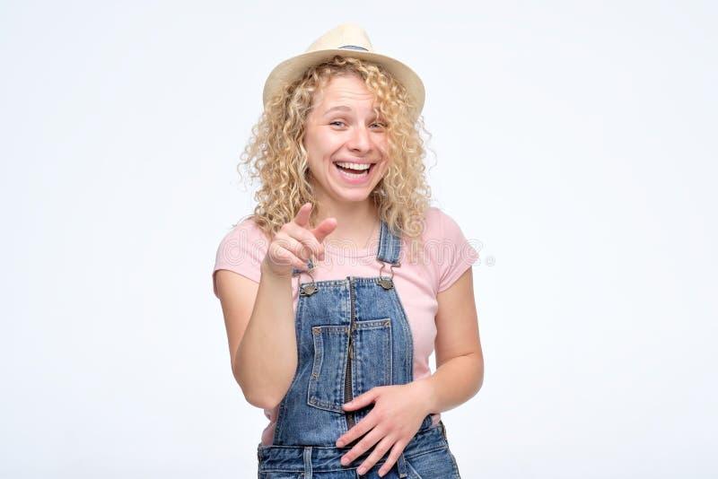 Junge gelockte Frau im Hut und Overall, die über Sie zeigen und lachen lizenzfreies stockfoto