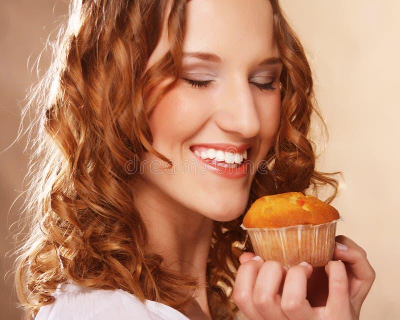 Junge gelockte Frau mit einem Kuchen lizenzfreie stockfotos