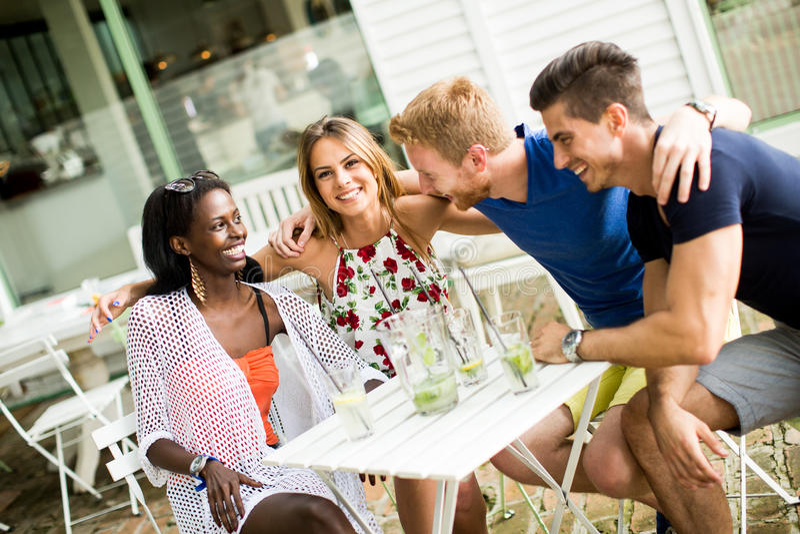 Junge gemischtrassige Freunde am Café stockfotografie