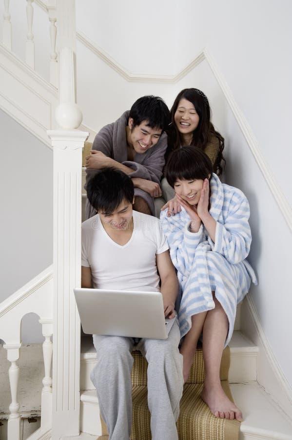 Junge genießende Paare bei der Anwendung des Laptops lizenzfreies stockbild