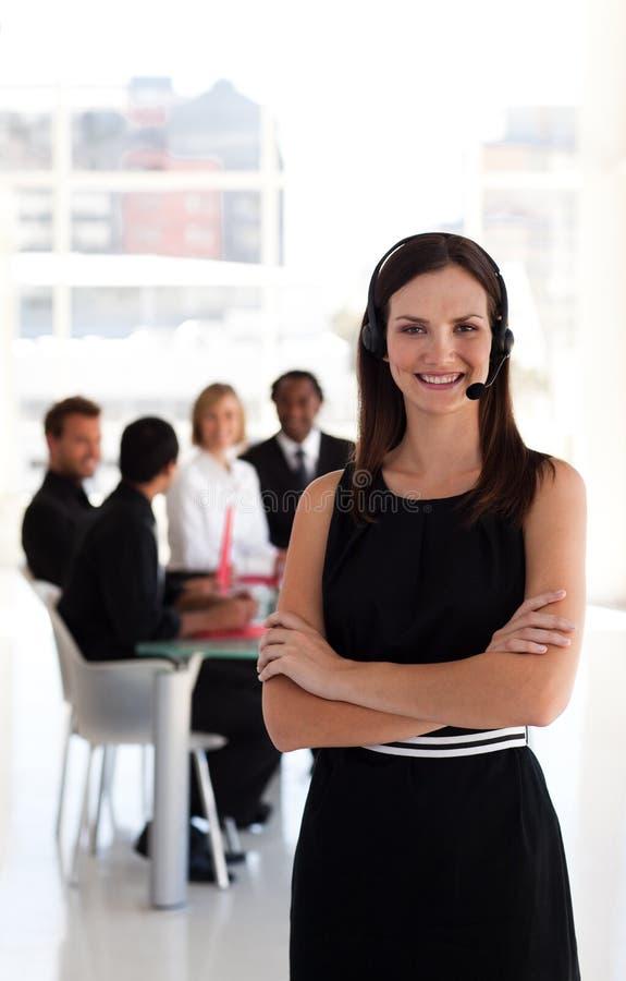 Junge Geschäftsfrau auf einem Kopfhörer lizenzfreie stockbilder