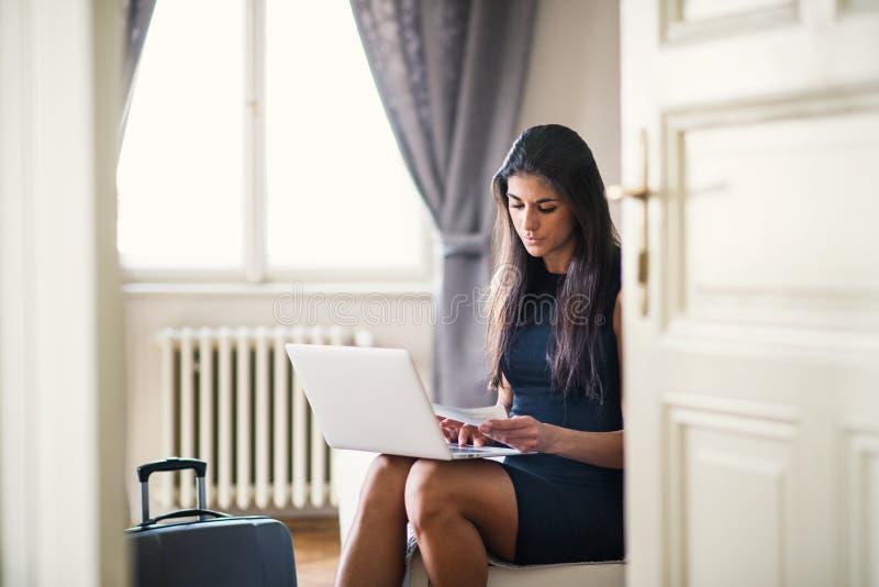 Junge Geschäftsfrau auf einer Geschäftsreise, die in einem Hotelzimmer, unter Verwendung des Laptops sitzt stockbild
