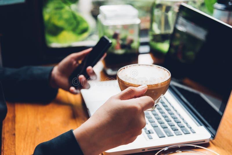 Junge Geschäftsfrau benutzt sein intelligentes Telefon und die Laptop-Computer lizenzfreies stockfoto