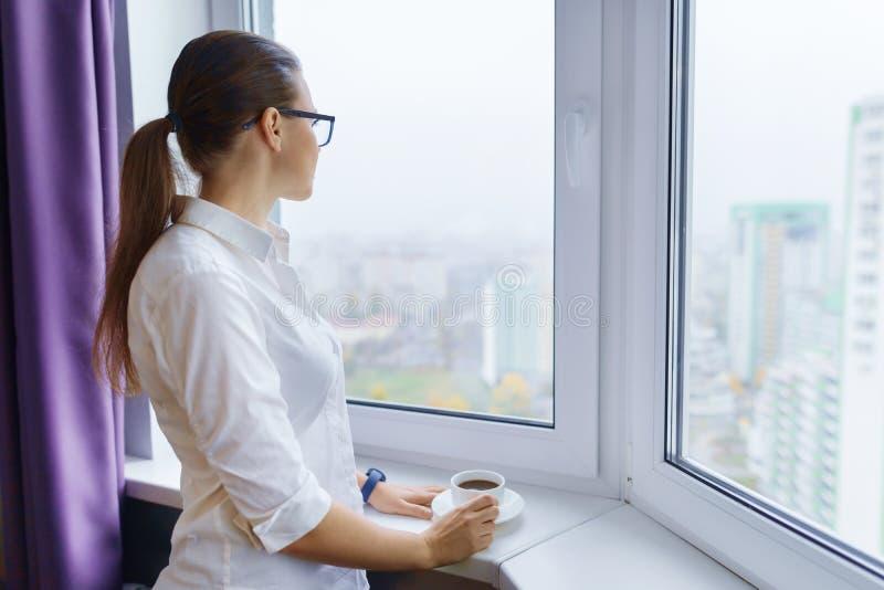 Junge Geschäftsfrau in den Gläsern mit einem Tasse Kaffee nahe dem Fenster, brunette Frau schaut heraus das Fensterlächeln lizenzfreie stockfotos