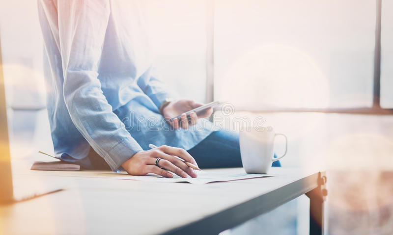 Junge Geschäftsfrau des Fotos, die mit neuem Startprojekt im modernen coworking Büro arbeitet Sitzende hölzerne Tabelle, halten stockfotografie