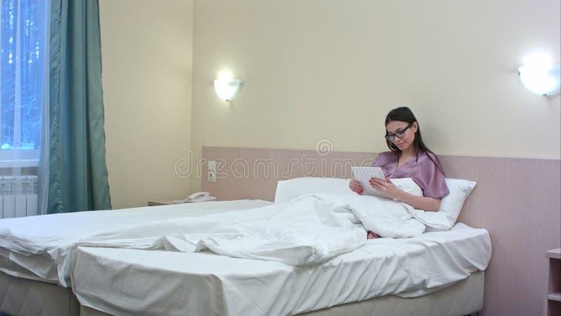 Junge Geschäftsfrau, die auf Bett in einem Hotelschlafzimmer unter Verwendung ihrer Tablette liegt stockfotografie