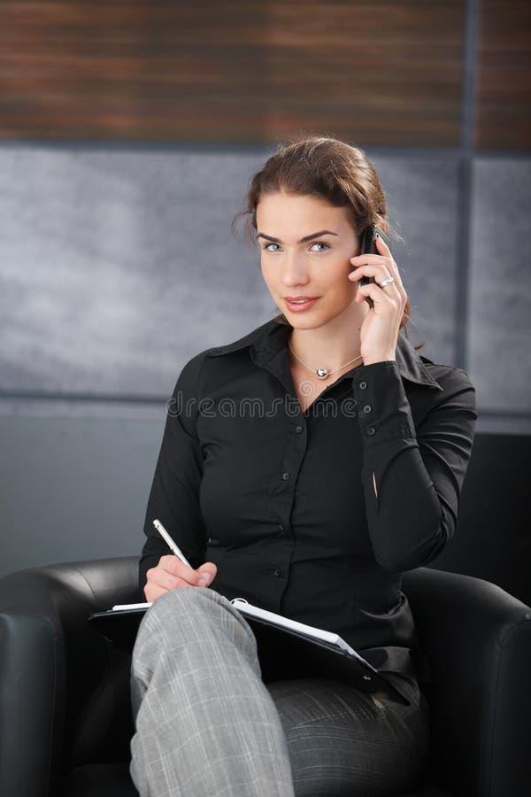 Junge Geschäftsfrau, die auf dem beweglichen Lächeln plaudert lizenzfreies stockfoto