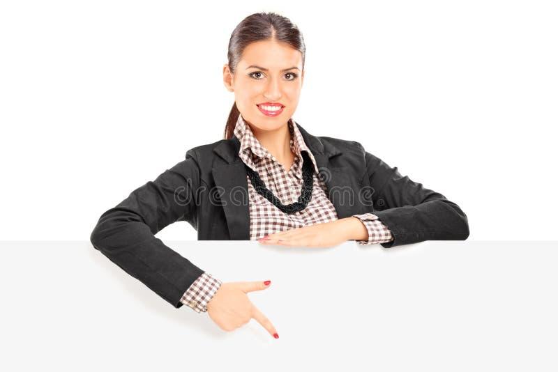 Junge Geschäftsfrau, die auf eine Leerplatte zeigt lizenzfreie stockbilder