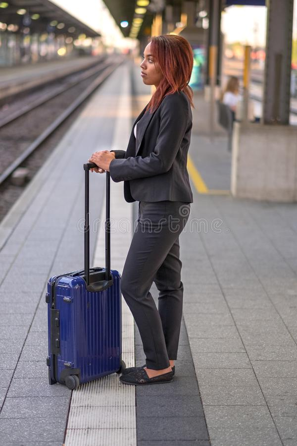 Junge Geschäftsfrau, die auf eine Plattform wartet stockfotos