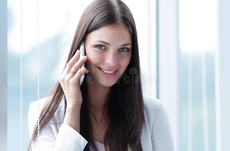 Junge Geschäftsfrau, die auf Handy spricht stockfoto