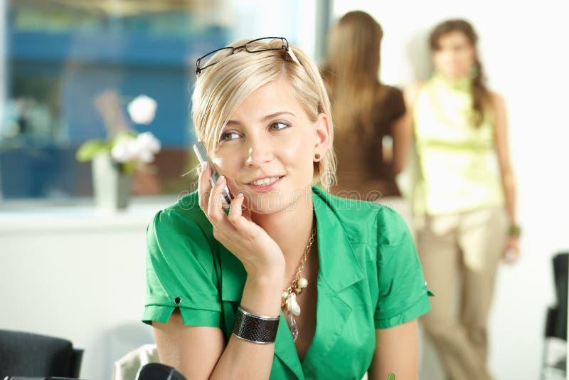 Junge Geschäftsfrau, die auf Mobile spricht stockfoto