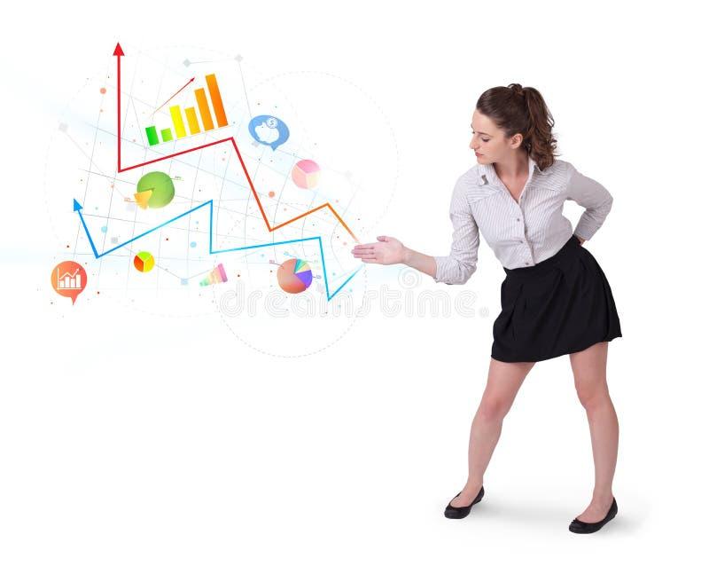 Junge Geschäftsfrau, die bunte Diagramme und Diagramme darstellt lizenzfreies stockbild