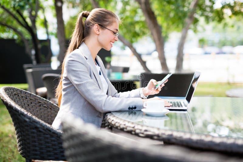 Junge Geschäftsfrau, die Café im im Freien arbeitet stockbild