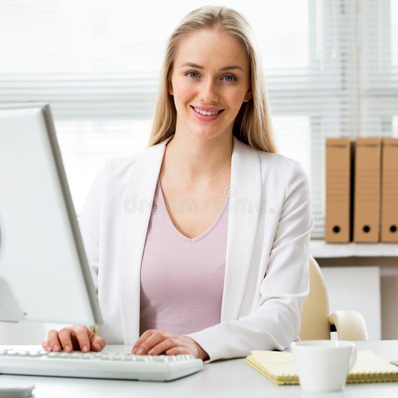Junge Geschäftsfrau, die Computer im Büro verwendet stockfotografie