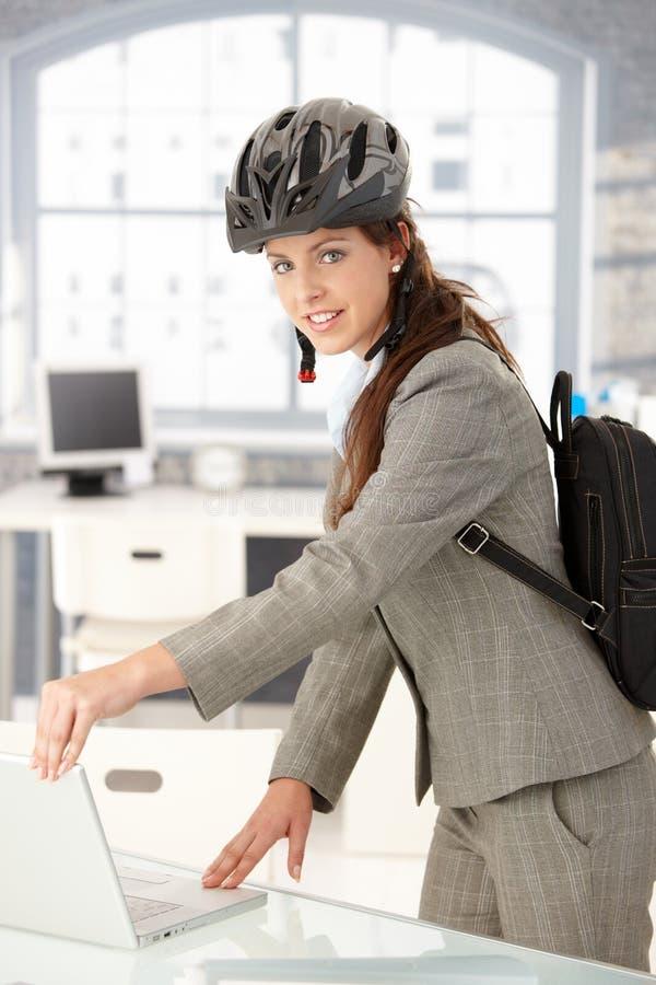Junge Geschäftsfrau, die das Amt durch das Fahrradlächeln niederlegt stockfotos