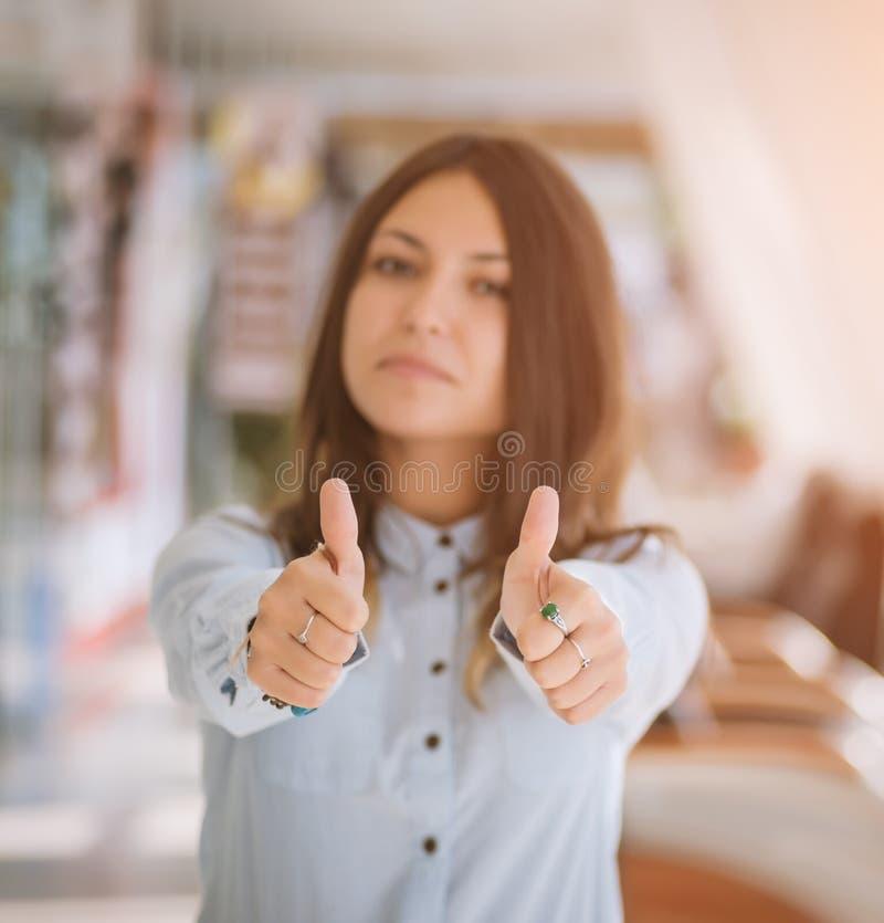 Junge Geschäftsfrau, die Daumen aufgibt stockbilder