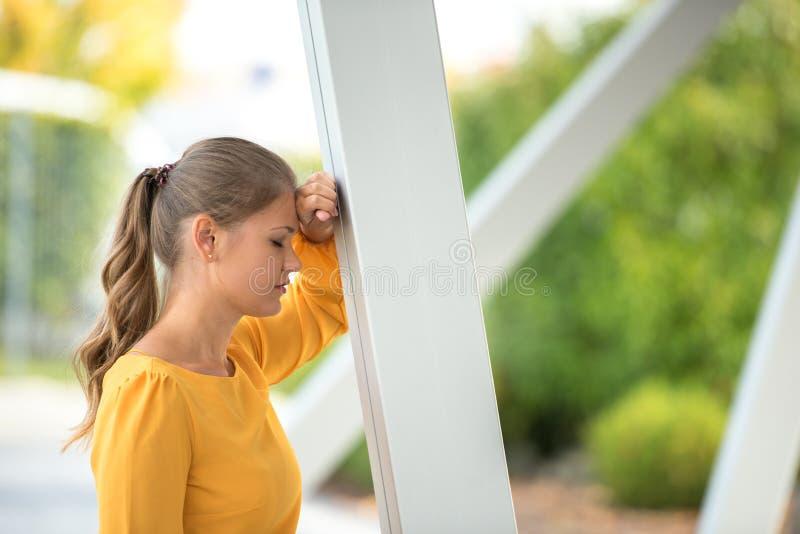 Junge Geschäftsfrau, die an der Spalte sich lehnt stockbild