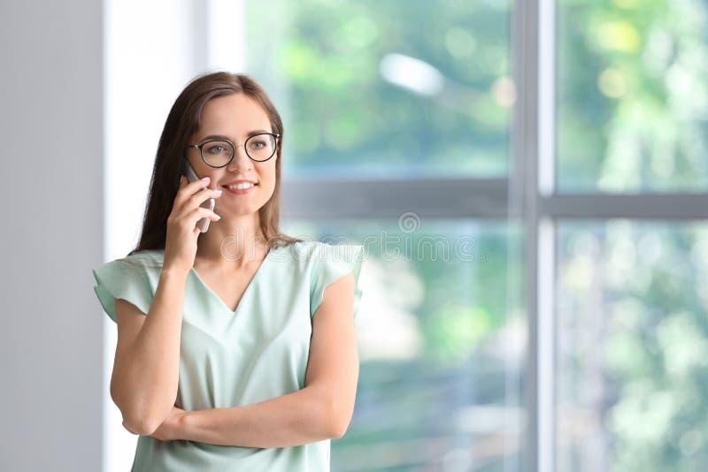 Junge Geschäftsfrau, die durch Handy im Büro spricht lizenzfreie stockbilder