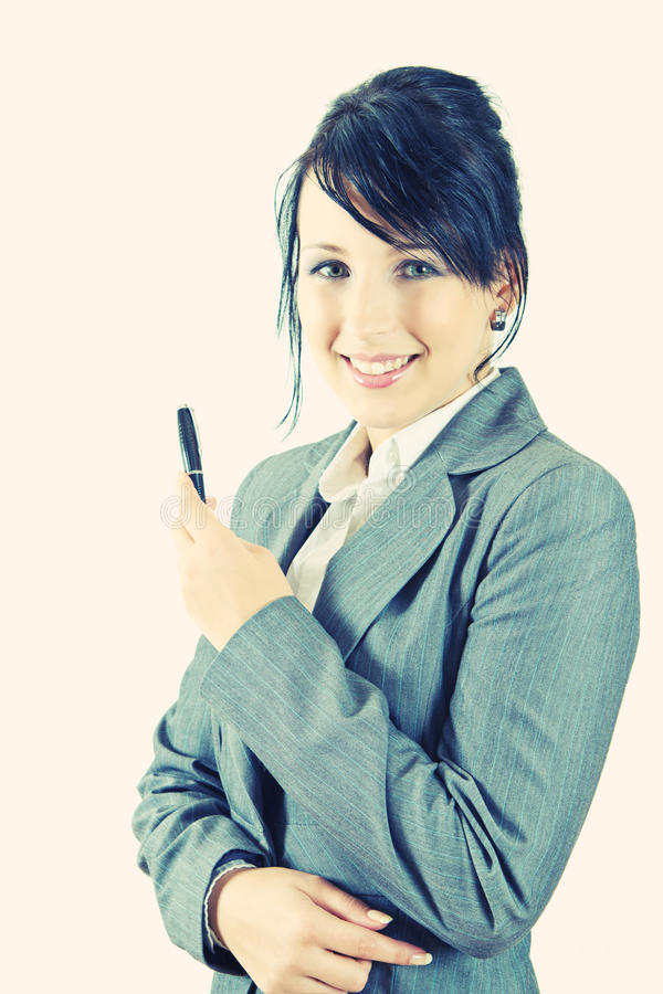 Junge Geschäftsfrau, die eine Feder anhalten lächelt lizenzfreie stockfotos