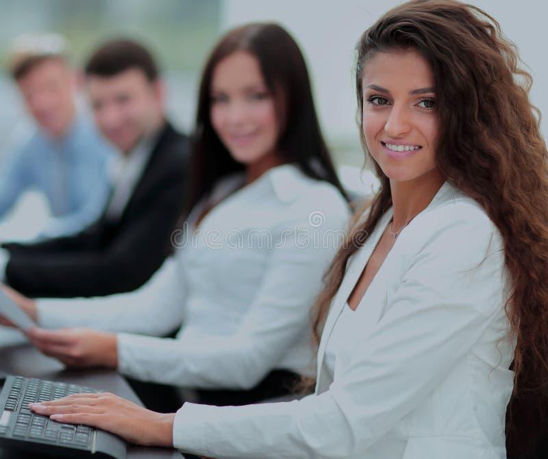 Junge Geschäftsfrau, die in einem Büro unter Verwendung des Computers mit Co arbeitet stockfotografie