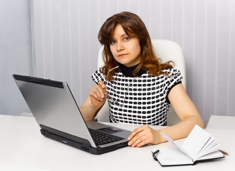 Junge Geschäftsfrau, die an einem Schreibtisch sitzt lizenzfreies stockbild
