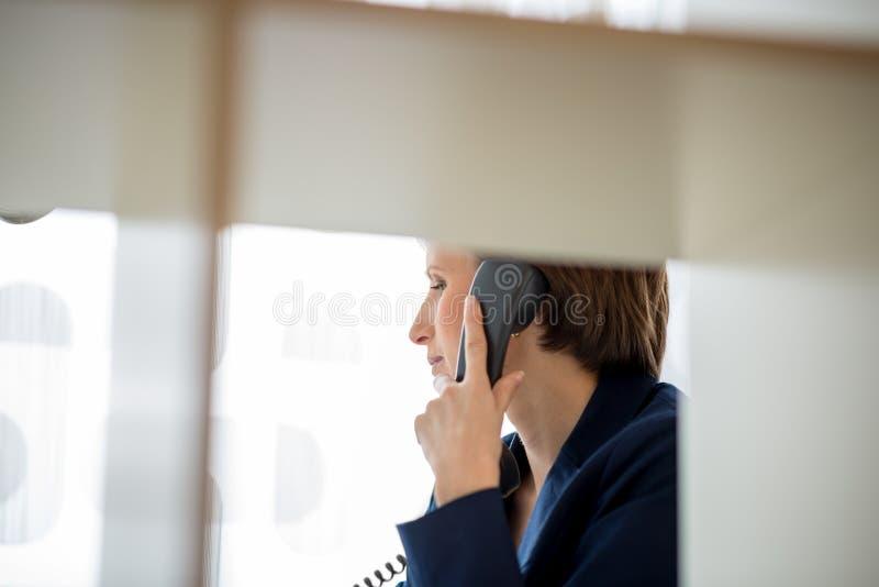 Junge Geschäftsfrau, die einen Anruf am Überlandleitungstelefon macht lizenzfreie stockbilder