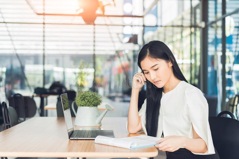Junge Geschäftsfrau, die einen Bericht ihre Hand hält einen Stift sitzt in einer Kaffeestube liest lizenzfreie stockfotos