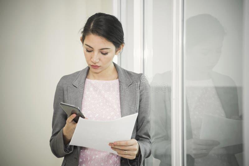 Junge Geschäftsfrau, die einen Smartphone für Arbeit im Büro verwendet stockbilder