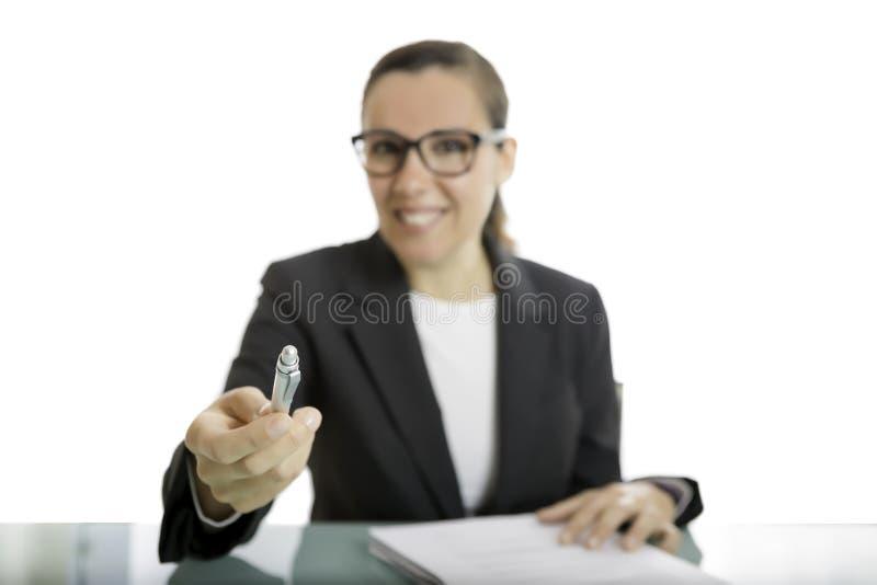 Junge Geschäftsfrau, die einen Stift anbietet stockfotos