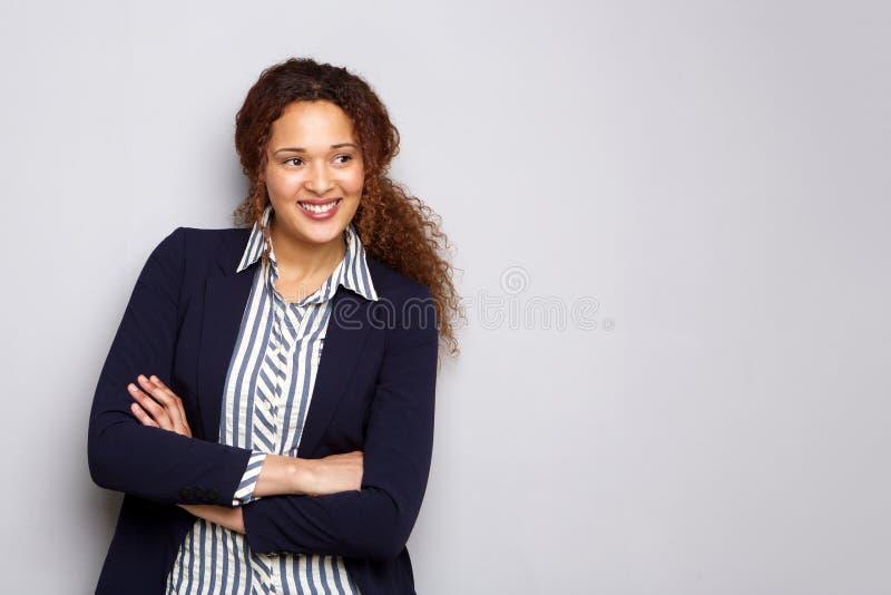 Junge Geschäftsfrau, die gegen grauen Hintergrund lächelt lizenzfreie stockbilder