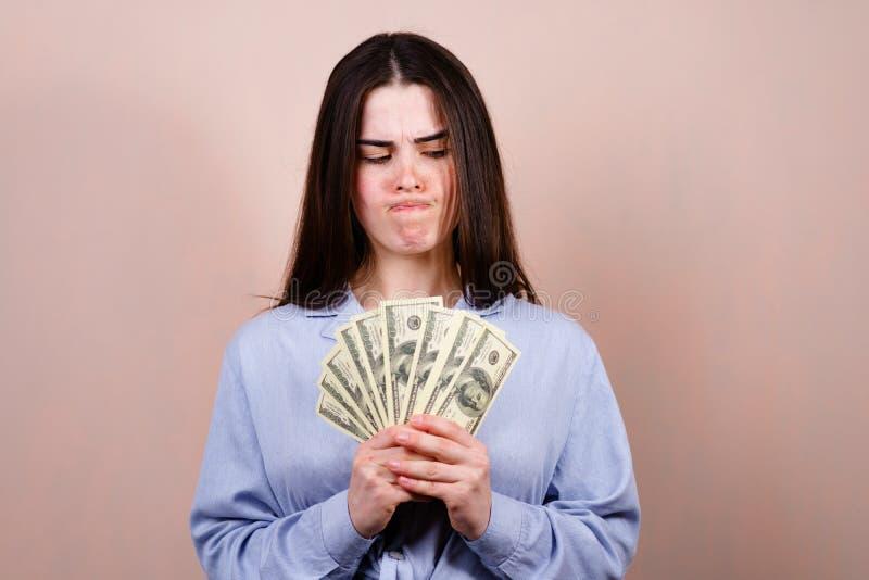 Junge Geschäftsfrau, die Geld mit Verzweiflung betrachtet lizenzfreies stockfoto
