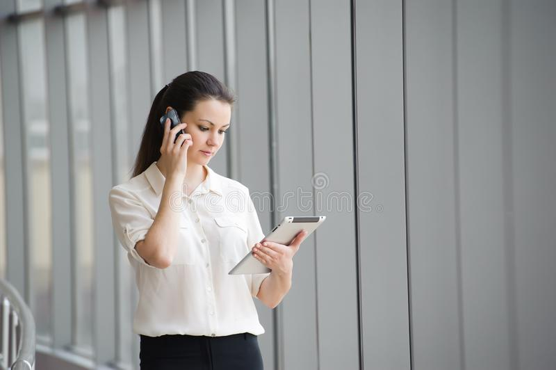 Junge Geschäftsfrau, die am Handy beim Bereitstehen des Fensters im Büro spricht Schönes junges weibliches Modell im Büro stockfoto