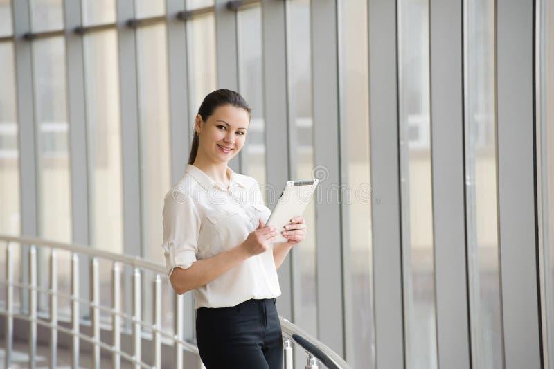 Junge Geschäftsfrau, die am Handy beim Bereitstehen des Fensters im Büro spricht Schönes junges weibliches Modell im Büro lizenzfreies stockfoto