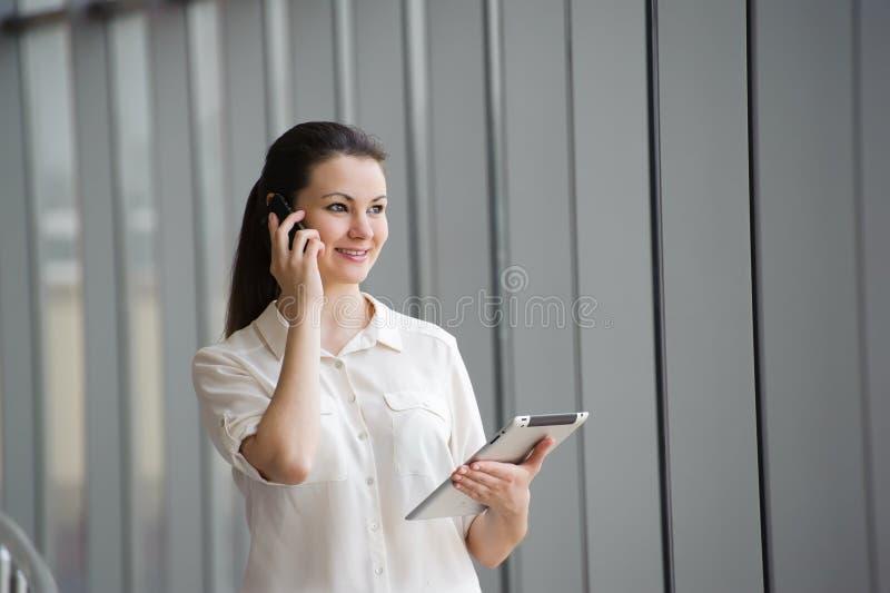Junge Geschäftsfrau, die am Handy beim Bereitstehen des Fensters im Büro spricht Schönes junges weibliches Modell im Büro lizenzfreies stockbild